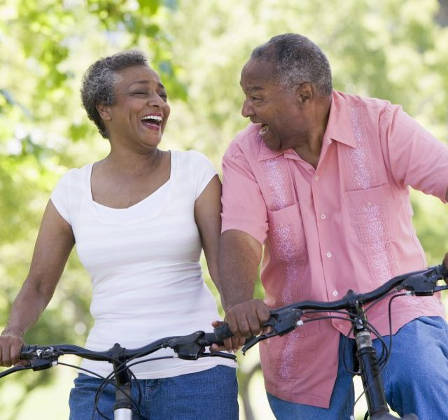 older man and woman riding bikes and laughing